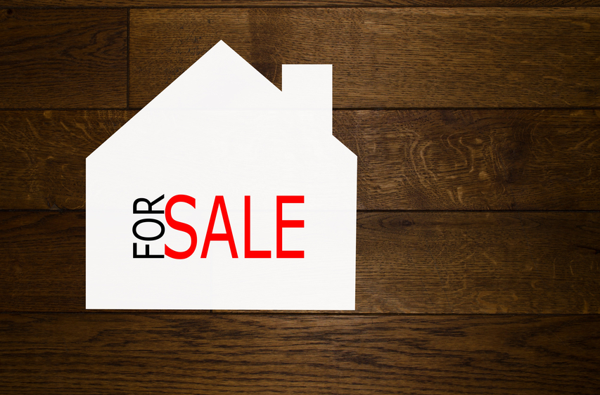 House for sale with text over wooden background