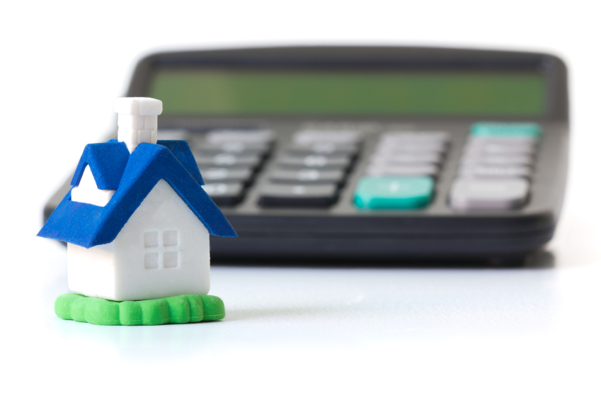 Miniature house in front of calculator concept for mortgage, home finances or saving for a house