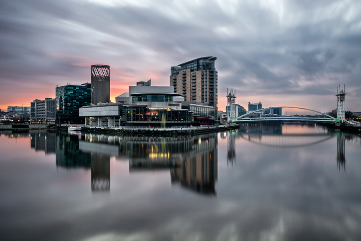 A beautiful vibrant pink/purple sunrise at Salford Quays in Greater Manchester, UK with clear mirror like reflections in the water. A long exposure was used to show motion in the moody sky.