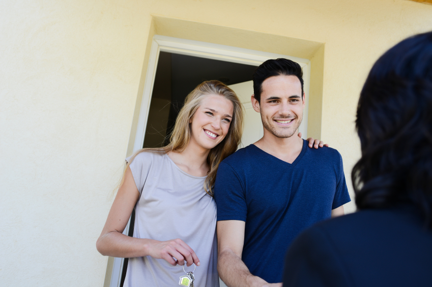 happy young couple with a real estate agent getting keys in front of their new house