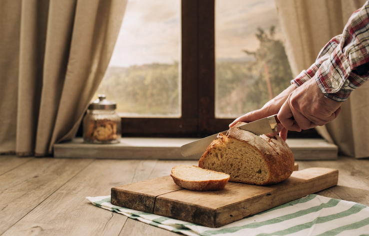 Man cutting a loaf of fresh bread in front of a window, country living and healthy food concept