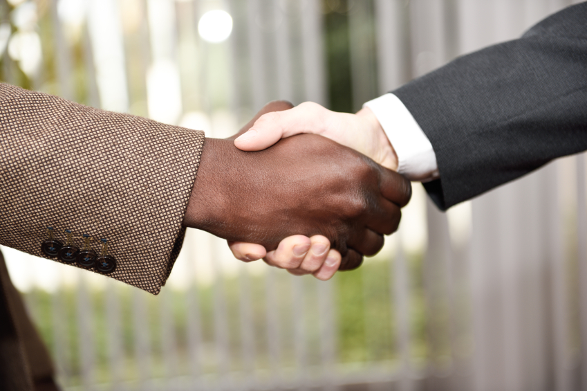 Black businessman shaking hands with a caucasian one wearing suit in a office. Close-up shot